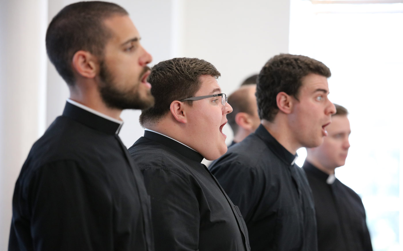 Seminarians sing with the Schola